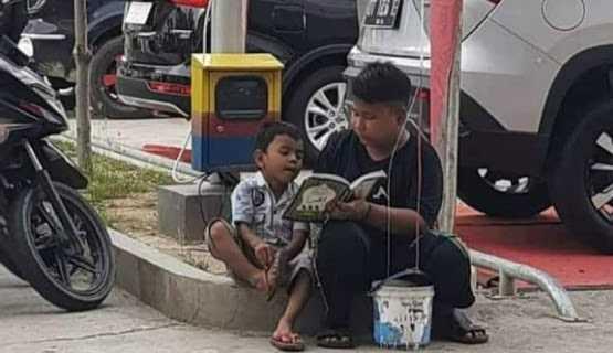Foto Kakak Penjual Balon Ajari Adik Baca Iqra di Parkiran